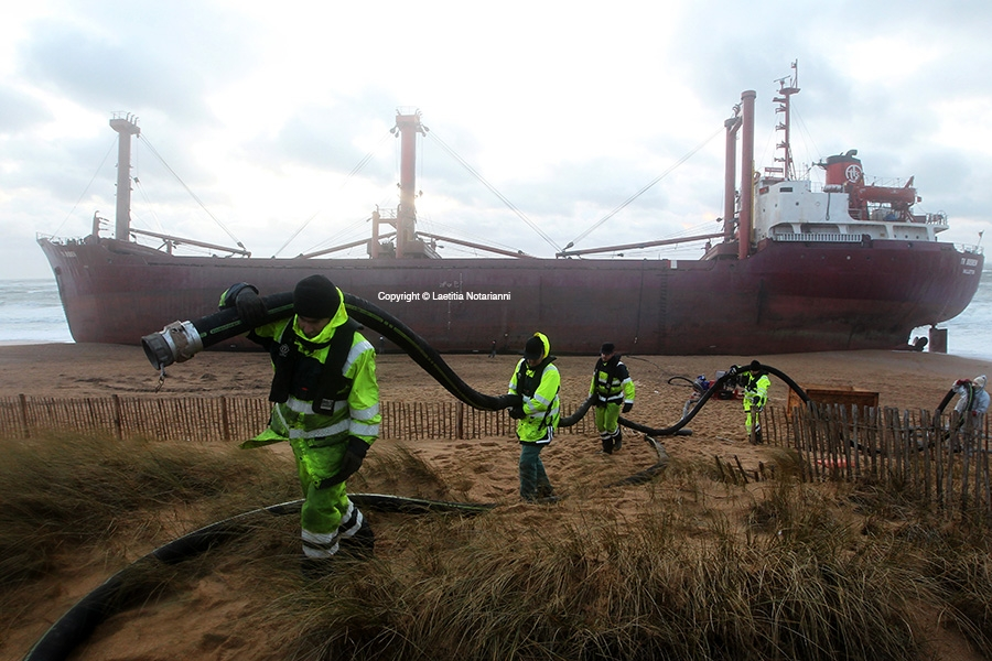 Rescue workers clean the beach after the TK Bremen cargo ship, which ran aground, spilling oil off the coast of France's northwestern region of Brittany and lies stranded on Kerminihy beach in Erdeven, France on December 16, 2011. Winter storm Joachim has battered France's western seabord since Thursday. Photo by Laetitia Notarianni/ABACAPRESS.COM